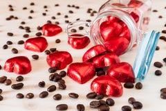 Corazones rojos en un tarro de cristal y granos de café Imágenes de archivo libres de regalías