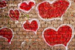 Corazones rojos pintados en una pared de ladrillo Imágenes de archivo libres de regalías