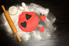 Corazones rojos que cortan la pasta con los huevos, la harina y el rodillo en una tabla negra Foto de archivo