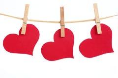 Corazones rojos que cuelgan en cuerda para tender la ropa Imagen de archivo libre de regalías