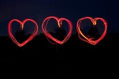 Corazones rojos triples que brillan en la noche. Fotos de archivo