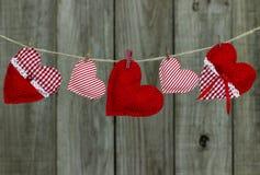 Corazones rojos y blancos de la tela del país que cuelgan en cuerda para tender la ropa por la cerca de madera Imagenes de archivo