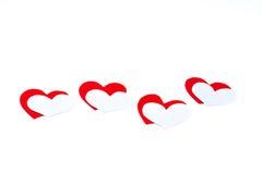 Corazones rojos y blancos en un fondo blanco Foto de archivo libre de regalías