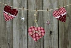 Corazones rojos y cerraduras en forma de corazón que cuelgan en cuerda para tender la ropa por la cerca de madera apenada Imagen de archivo