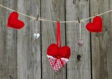 Corazones rojos y cerraduras que cuelgan de cuerda para tender la ropa por la cerca de madera rústica Imágenes de archivo libres de regalías