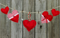 Corazones rojos y cerraduras que cuelgan en cuerda para tender la ropa por la cerca de madera rústica Imagen de archivo libre de regalías