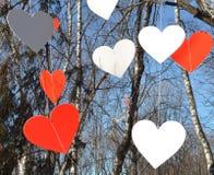 Corazones rojos y corazones blancos contra el cielo azul y árboles Fotos de archivo