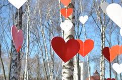 Corazones rojos y corazones blancos contra el cielo azul y árboles Fotografía de archivo libre de regalías