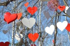 Corazones rojos y corazones blancos contra el cielo azul y árboles Imagenes de archivo