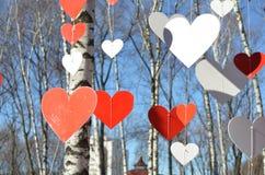 Corazones rojos y corazones blancos contra el cielo azul y árboles Fotos de archivo libres de regalías