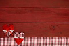 Corazones rojos y frontera roja de la tela de la guinga en muestra de madera roja antigua Foto de archivo