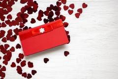 Corazones rojos y tarjeta que ponen en la tabla blanca de madera Día del `s de la tarjeta del día de San Valentín Foto de archivo