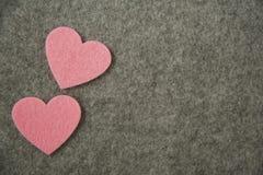 Corazones rosados en fondo del fieltro del gris Fotografía de archivo