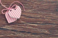 Corazones rosados en tarjeta de madera Fotos de archivo