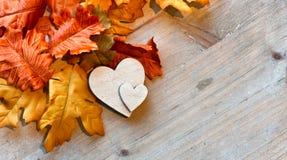 Corazones y Autumn Leaves de madera Foto de archivo libre de regalías