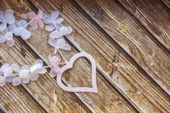 Corazones y flores rosados y blancos en una tabla de madera Fotos de archivo
