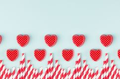 Corazones y paja rojos brillantes del cóctel como frontera decorativa en fondo de papel en colores pastel de la menta Concepto de fotografía de archivo