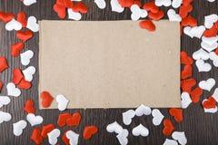 Corazones y tarjeta rojos y blancos en un fondo de madera oscuro Imágenes de archivo libres de regalías