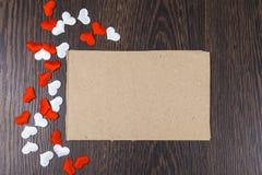 Corazones y tarjeta rojos y blancos en un fondo de madera oscuro Imagen de archivo