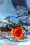 Corbata coloreada con las rosas rojas en un fondo azul Imagen de archivo