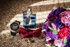 Corbata de lazo, anillos de bodas, reloj, perfumes, la mañana del novio, negocio Imagen de archivo
