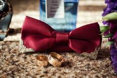 Corbata de lazo, anillos de bodas, reloj, perfumes, la mañana del novio, negocio Fotos de archivo