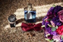 Corbata de lazo, anillos de bodas, reloj, perfumes, la mañana del novio, negocio Imagen de archivo libre de regalías