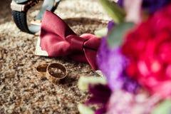 Corbata de lazo, anillos de bodas, reloj, perfumes, la mañana del novio, negocio Fotografía de archivo