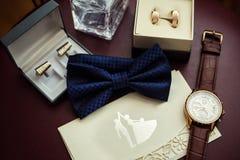 Corbata de lazo, anillos de bodas en la caja, reloj, parfumes, mancuernas, Invitatio Imagenes de archivo