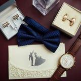 Corbata de lazo, anillos de bodas en la caja, reloj, parfumes, mancuernas, Invitatio Fotografía de archivo libre de regalías