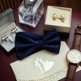 Corbata de lazo, anillos de bodas en la caja, reloj, parfumes, mancuernas, Invitatio Foto de archivo libre de regalías