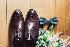 Corbata de lazo azul, zapatos de cuero y anillos de bodas Novios que se casan mañana Ciérrese para arriba de los accesorios del h Fotografía de archivo