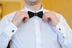 Corbata de lazo de los tactos de las manos del hombre en un traje Fotografía de archivo libre de regalías
