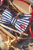 Corbata de lazo elegante en la caja del arte en la arena ` S de los hombres y accesorios del ` s de las mujeres en el fondo de la Fotos de archivo