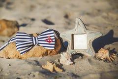 Corbata de lazo elegante en marco de la piedra y de la foto en la playa ` S de los hombres y accesorios del ` s de las mujeres en Foto de archivo