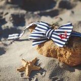 Corbata de lazo elegante en piedra en la playa ` S de los hombres y accesorios del ` s de las mujeres en el fondo de la playa are Imagenes de archivo