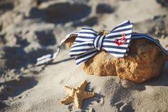 Corbata de lazo elegante en piedra en la playa ` S de los hombres y accesorios del ` s de las mujeres en el fondo de la playa are Imagen de archivo