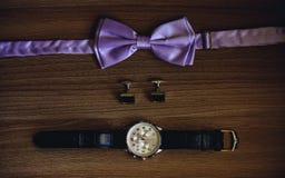 Corbata de lazo, mancuernas y relojes en fondo de madera Foto de archivo libre de regalías