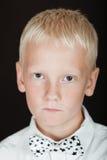 Corbata de lazo que lleva del muchacho rubio enojado con las estrellas negras Fotos de archivo