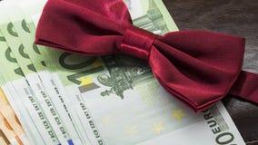 Corbata de lazo roja contra la perspectiva del dinero euro fotos de archivo libres de regalías
