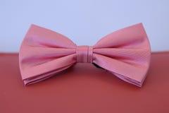 Corbata de lazo rosada con el modelo sedoso de la raya colocado en un amortiguador de cuero rojo contra un fondo borroso Imagen de archivo