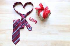 Corbata del coraz?n y caja de regalo roja con la cinta roja y coraz?n hecho a mano del ganchillo en el fondo de madera para el d? fotos de archivo libres de regalías