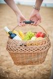Corbeille de fruits et vin dans les mains Photographie stock libre de droits