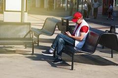 Corby,英国- 2018年9月, 01日:读报纸的成人人在街道的长凳 库存图片