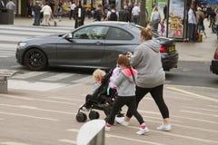 Corby, het Verenigd Koninkrijk - augustus 28, 2018: Jonge moeder die in straat met twee kinderen en kinderwagen lopen Actieve fam royalty-vrije stock foto's