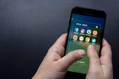 Corby, Reino Unido - 27 de janeiro de 2019: Mulher que usa um smartphone com ícones de meios sociais na tela, estilo de vida do s fotos de stock