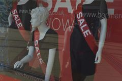 Corby, U k , Il 20 giugno 2019 - manichino in una finestra del negozio con l'iscrizione di vendita Di vendita di tempo vestiti di immagini stock libere da diritti