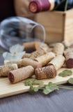 Corchos del vino en la tabla con el vidrio y la botella en el fondo Fotos de archivo libres de regalías