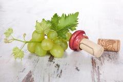 Corchos del vino, uvas blancas y hojas del vino. Foto de archivo libre de regalías