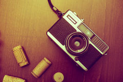 Corchos retros de la cámara y del vino en el fondo de madera de la tabla, vintage co Fotografía de archivo